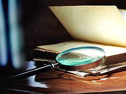 A magnifying glass on a table with a book in the background