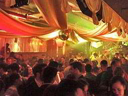 A view over a filled dance floor with white canvas above, and orange lighting