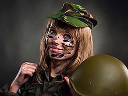 Close up of a woman in camouflage and face paint, holding a green helmet