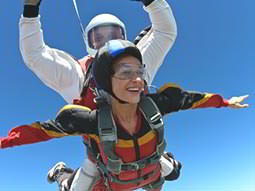 A woman skydiving with an instructor on her back