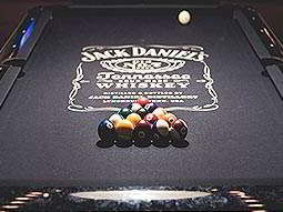 A black pool table set up for a game