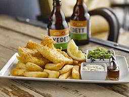 A plate of fish and chips, with two bottles of Vedett beer in the background