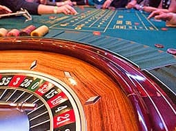 A roulette wheel with people playing on the table in the background
