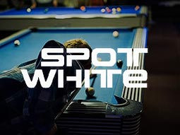 A man lining up a shot on a blue pool table, with another table visible in the background