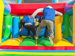 Some men running onto a multicoloured bouncy castle