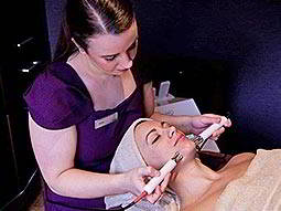 A woman receiving a facial, whilst wearing a white towel on her head