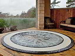 A Jacuzzi bubbling away with decking surrounding it