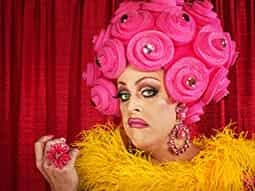 A man dressed as a drag queen, in a bright pink wig and yellow feather dress