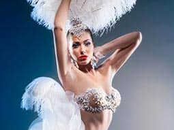 A woman wearing burlesque clothing, including huge white feathers and a sparkly bra