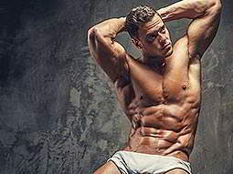 A man wearing only white underpants, posing with all of his muscles