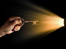 A person holding a key, with light shining through a small hole onto the aforementioned key