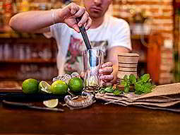 A man making a cocktail using limes on a bar