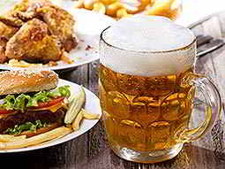 A stein full of beer with some food surrounding it
