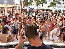 The back of a DJs head, performing to a crowd at a beach club