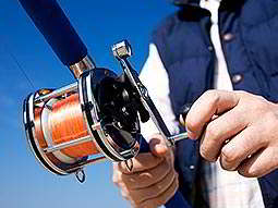 A man's hand holding a fishing rod