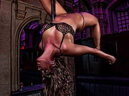 A woman bending backwards around a stripper pole