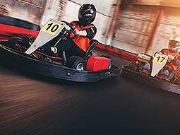 Two people in red overalls, racing go karts on an indoor track