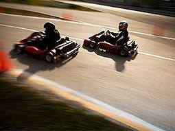 Two people racing on an outdoor track in karts