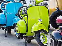 A green vespa parked in the street, with a blue one parked behind