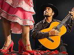 A man playing a guitar, and looking up to a woman wearing a flamenco outfit