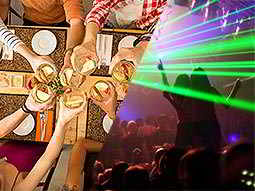 A split image of people clinking their glasses together and a club with green laser lights