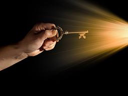 A person's hand reaching out to light with a brass key