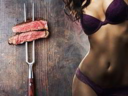 A woman's body in purple underwear, tiled next to a skewer of meat against a wooden table