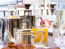 A breakfast table with metal teapots, champagne and juice