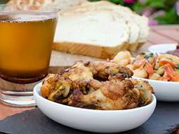 Two white bowls of tapas with a beer and bread in the background