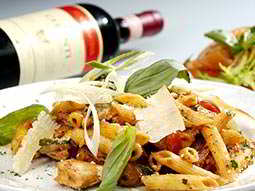 Plate of pasta with a bottle of red wine on its side, in the background