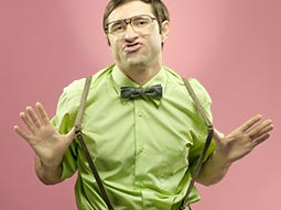 A geek male wearing a shirt and bow tie and pulling on his braces