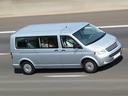 A silver minibus driving on a road