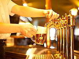A man's hand pouring a beer from a beer tap