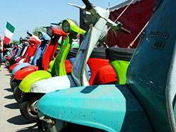 A line of colourful vespas, parked up in a street during the day