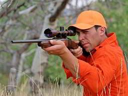 A man wearing an orange cap and jacket, firing a gun