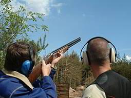 One man and a helper firing a gun into the sky
