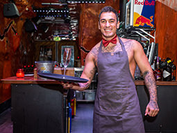 A butler wearing a bow tie and an apron holding a tray of drinks