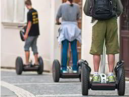 A line of the back of three people riding Segways in a street