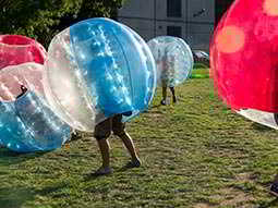 People playing on an outdoor pitch in inflatable zorbs