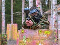 A man aiming his paintball gun over a wooden obstacle