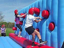 Competitors tackling a wall with obstacles to pass by