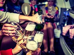 A group of people  in a party bus clinking their champagne glasses together