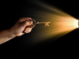 A man's hand holding a key to a light coming through a door