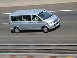 A grey minibus driving down a road