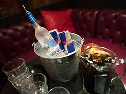 Ice bucket with bottles of vodka in, on a bar top, with spirits stacked in the background