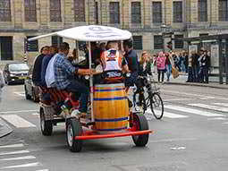 A group of men on a beer bike in the street
