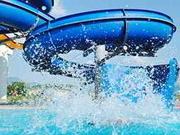 A person landing in a pool from a blue, outdoor slide