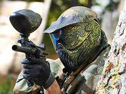 A man in a helmet and gloves, peeping out from a wall whilst brandishing a paintball gun