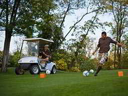 A man in golf attire, kicking a football on a golf course with a man sat in a golf buggy in the background