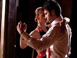 A close of a man and woman salsa dancing
